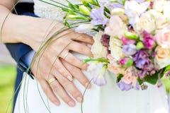 Hände und Ringe auf Hochzeitsblumenstrauß Stockfotos
