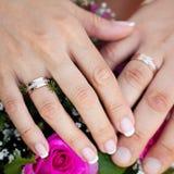 Hände und Ringe auf Hochzeitsblumenstrauß Stockbilder