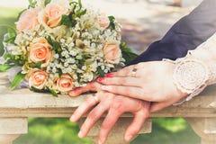 Hände und Ringe auf Hochzeitsblumenstrauß Lizenzfreie Stockfotos