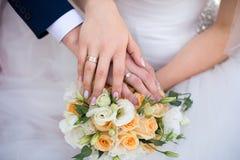 Hände und Ringe auf Hochzeitsblumenstrauß Stockbild