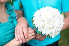 Hände und Ringe auf Hochzeitsblumenstrauß Lizenzfreie Stockfotografie