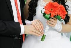Hände und Ringe mit Hochzeitsblumenstrauß von orange Gerberas lizenzfreies stockbild