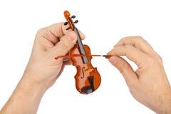 Hände und Spielzeugvioline Stockfoto