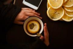 Hände und Tee mit Zitrone lizenzfreie stockbilder