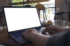 Hände unter Verwendung des Laptops mit leerem weißem Tischplattenschirm mit Kaffeetasse und Kuchen auf Holztisch im Café Stockbilder