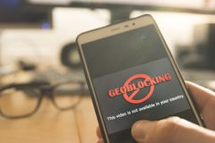 Hände unter Verwendung eines Smartphone mit dem Geo-Blockieren auf Schirm Lizenzfreies Stockfoto