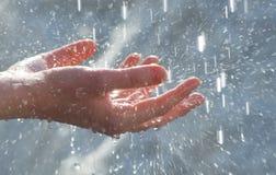 Hände unter Wassertropfen Stockfotografie