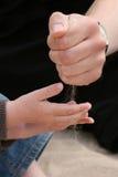 Hände - Vater und Kind, die mit Sand spielen Stockbilder