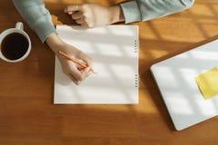 Hände von Asiatinnen nehmen Kenntnisse über den Holztisch lizenzfreies stockfoto
