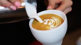 Hände von barista des Latte- oder Cappuccinomachend die auslaufende Milch Kaffees, die Lattekunst macht stock footage