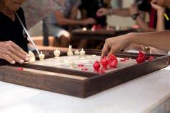 Hände von den älteren Männern, die thailändisches Schach spielen Stockbild