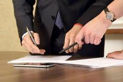 Hände von den Geschäftsleuten und Frauen, welche die Dokumente studieren stockbild