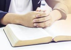 Hände von den Männern, die auf offener Bibel beten, buchen Stockfotografie