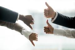 Hände von den verschiedenen Geschäftsleuten, die auf und ab Daumen zeigen lizenzfreie stockbilder