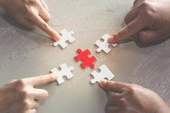 Hände von den verschiedenen Leuten, die Puzzlen, Hilfsunterstützung zusammenbauen stockfotografie