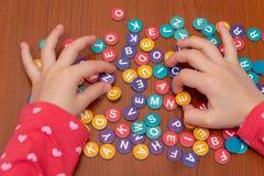 Hände von Mädchen auf einem Holztisch fügen ein Puzzlespiel von farbigen Buchstaben, hinzufügen ein Wort von farbigen Buchstaben, lizenzfreie stockfotos