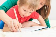 Hände von Mutter- und Kinderschreibensbuchstaben Stockfotos