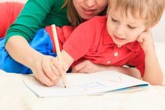 Hände von Mutter- und Kinderschreibensbuchstaben Stockbild