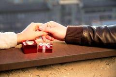 Hände von Paaren und öffnen roten Kasten mit goldenem Herzen Stockfoto