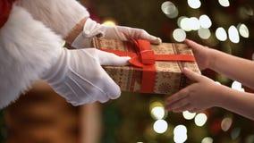 Hände von Santa Claus ein Weihnachtsgeschenk gebend dem Kind stock video footage