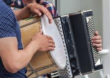 Hände von Straßenmusikern mit einer Trommel und einem alten Akkordeon Lizenzfreies Stockbild
