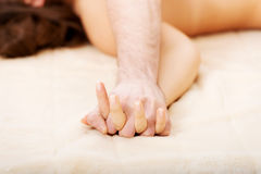 Hände von weiblichem und von Mann liegend auf Bett Lizenzfreie Stockfotografie