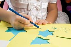 Hände von Zeichnung und Ausschnitt des kleinen Mädchens Weihnachtspapierzahlen Lizenzfreie Stockfotos