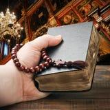 Hände, welche die Bibel anhalten und mit einem Rosenbeet beten lizenzfreies stockfoto