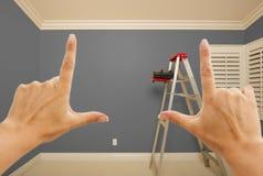 Hände, welche die graue gemalte Wand Innen gestalten lizenzfreie stockbilder