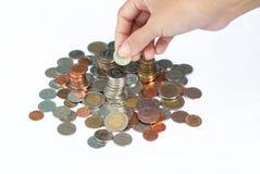 Hände, welche die Münzen lokalisiert auf weißen Hintergrund setzen stockbilder