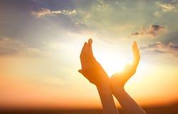 Hände, welche die Sonne anhalten Stockbild