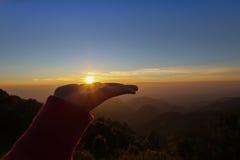 Hände, welche die Sonne bei Sonnenaufgang halten Lizenzfreie Stockfotos