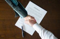 Händedruck über unterzeichnetem Vertrag stockfoto