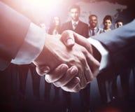 Händedruck auf der Hintergrundgruppe von Geschäftsleuten in den dunklen Farben lizenzfreie stockbilder