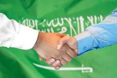 Händedruck auf Saudi-Arabien Flaggenhintergrund stockfotografie