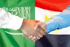 Händedruck auf Saudi-Arabien und Ägypten-Flagge Hintergrund lizenzfreie stockfotos