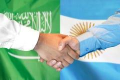 Händedruck auf Saudi-Arabien und Argentinien-Flagge Hintergrund stockfotos