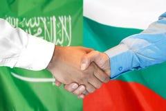 Händedruck auf Saudi-Arabien und Bulgarien-Flagge Hintergrund lizenzfreies stockfoto