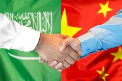 Händedruck auf Saudi-Arabien und China-Flagge Hintergrund lizenzfreies stockfoto