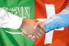 Händedruck auf Saudi-Arabien und die Schweiz-Flagge Hintergrund stockfotos