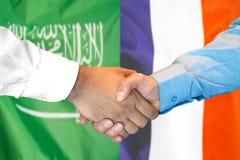 Händedruck auf Saudi-Arabien und Frankreich-Flagge Hintergrund stockfotografie
