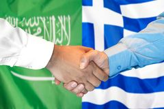 Händedruck auf Saudi-Arabien und Griechenland-Flagge Hintergrund lizenzfreie stockfotografie