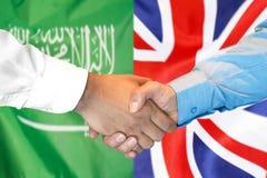Händedruck auf Saudi-Arabien und Großbritannien-Flaggenhintergrund lizenzfreie stockfotos
