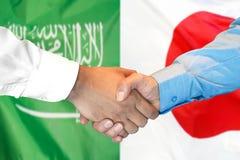 Händedruck auf Saudi-Arabien und Japan-Flagge Hintergrund stockfotografie
