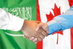 Händedruck auf Saudi-Arabien und Kanada-Flagge Hintergrund lizenzfreies stockbild