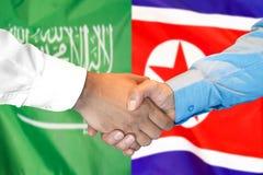 Händedruck auf Saudi-Arabien und Nordkorea-Flagge Hintergrund stockfoto