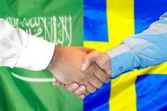 Händedruck auf Saudi-Arabien und Schweden-Flagge Hintergrund stockbilder
