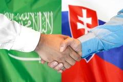 Händedruck auf Saudi-Arabien und Slowakei-Flagge Hintergrund stockbild