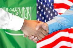 Händedruck auf Saudi-Arabien und US-Flaggenhintergrund lizenzfreie stockbilder