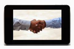 Händedruck auf Tablette Stockbilder